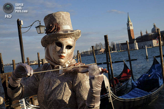 A masked reveller poses in Saint Mark's Square during the Venetian Carnival in Venice